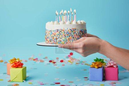 Foto de Recorta la vista de la mujer que sostiene el pastel de cumpleaños con velas sobre fondo azul con confeti y regalos - Imagen libre de derechos