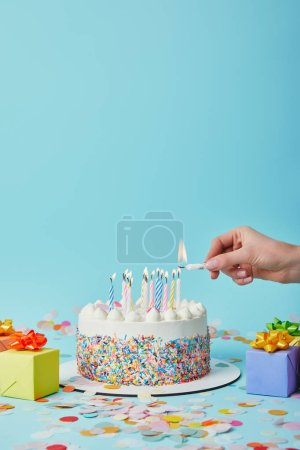Photo for Partial view of woman lighting birthday cake on blue background with gifts and confetti - Royalty Free Image