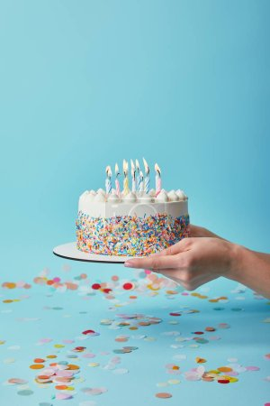 Photo for Cropped view of woman holding delicious birthday cake with candles on blue background with confetti - Royalty Free Image