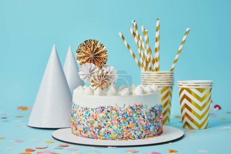 Delicious cake, plactic cups, party hats and drinking straws on blue background with confetti