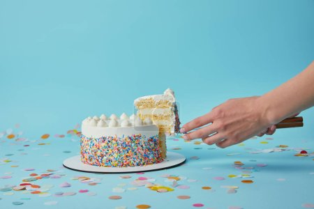 Photo for Partial view of woman taking piece of delicious cake on blue background - Royalty Free Image