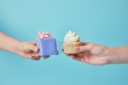 Cropped view of women holding delicious cupcake and gift on blue background