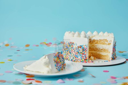 Photo for Slice of cake with cut cake on blue background with confetti - Royalty Free Image