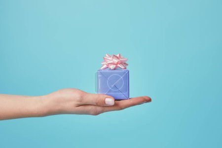 Partial view of woman holding gift with pink bow on blue background