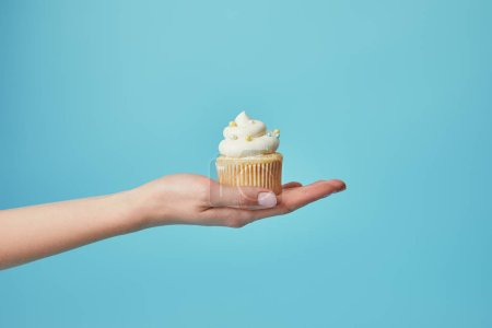 Photo for Partial view of woman holding tasty cupcake with sugar sprinkles on blue background - Royalty Free Image