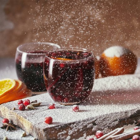 homemade mulled wine with cranberries and falling powdered sugar in kitchen