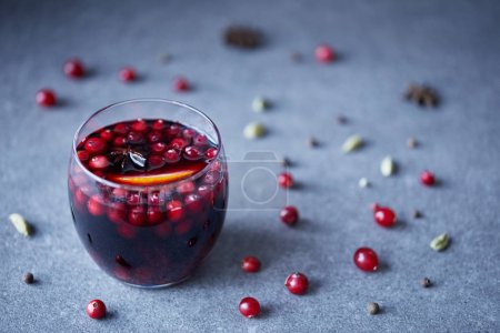glass of tasty homemade mulled wine with cranberries and orange, scattered berries on tabletop in kitchen