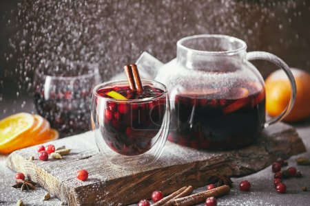 homemade mulled wine with cranberries in glasses and teapot with falling powdered sugar on table in kitchen