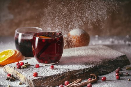 Photo for Hot homemade mulled wine with cranberries with falling powdered sugar on table in kitchen - Royalty Free Image