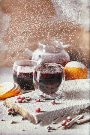 Foto de En polvo azúcar en dos vasos de vino caliente con especias sabroso con arándanos sobre mesa de cocina - Imagen libre de derechos