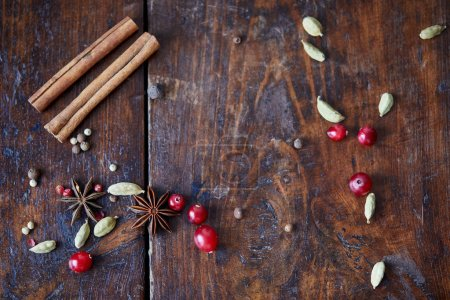 top view of scattered cranberries, cinnamon sticks and carnation on wooden table in kitchen