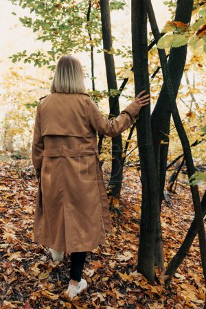 Back view of woman standing in autumn forest and touching tree trunk