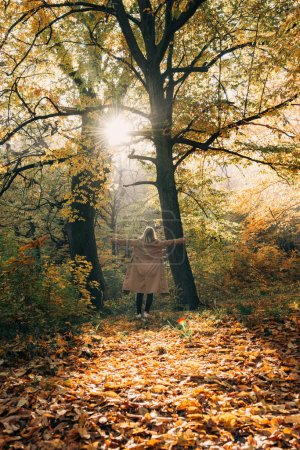 Back view of woman standing with spread hands in autumn forest