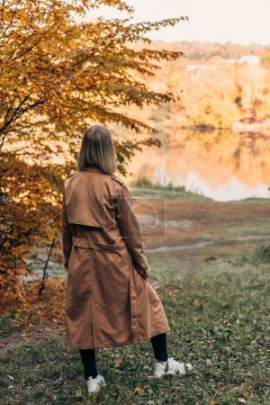 Back view of woman standing and looking at lake in autumn forest