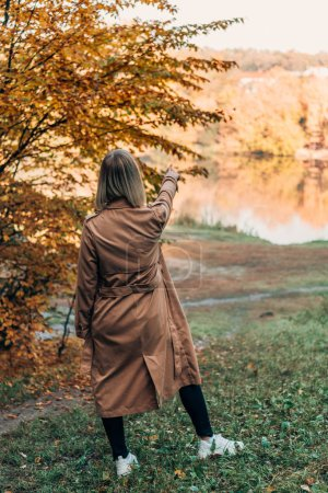 Back view of woman standing in coat and pointing at lake in autumn forest