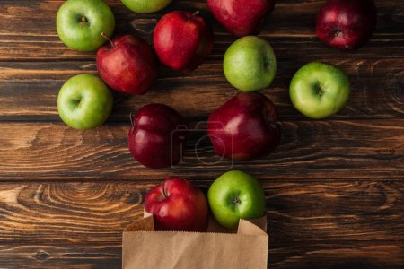 top view of scattered red and green apples with paper bag on wooden table