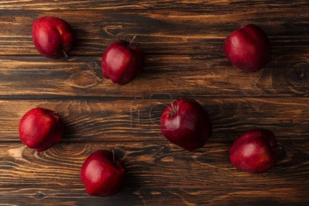 top view of ripe red delicious apples on wooden table