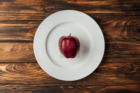 Photo for Top view of white plate with red delicious apple on wooden table - Royalty Free Image