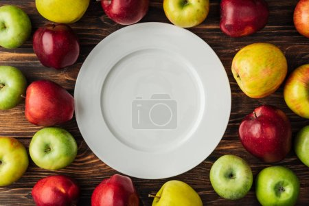 Photo for Top view of white plate and ripe multicolored apples on wooden table - Royalty Free Image