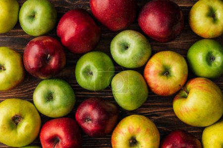Photo for Top view of ripe multicolored apples on wooden table - Royalty Free Image