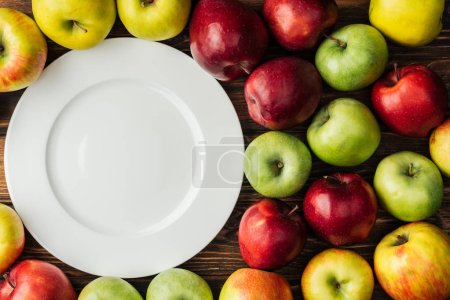 top view of white plate and multicolored apples on wooden table