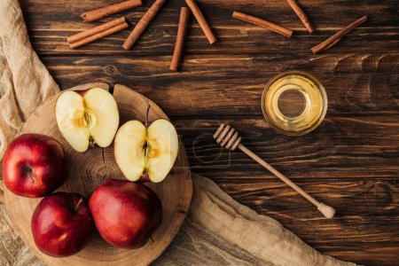 top view of red delicious apples, honey, cinnamon and fabric on wooden table