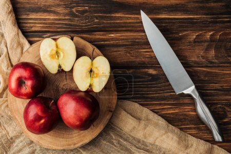 top view of red delicious apples on stump, knife and fabric on wooden table