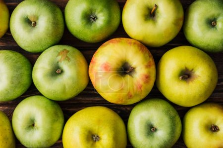 Photo for Top view of ripe green and golden apples on wooden table - Royalty Free Image