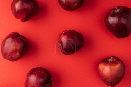 top view of delicious large apples on red background