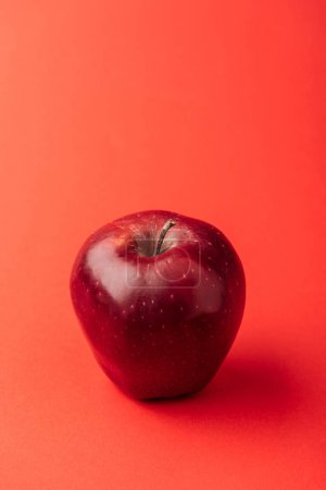 delicious large apple on red background