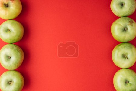 vertical frame of ripe green apples on red background