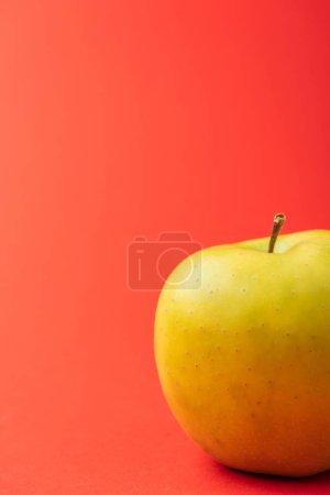 Foto de Cerrar vista de manzana deliciosa dorada sobre fondo rojo - Imagen libre de derechos