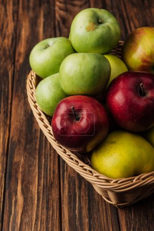 Photo for Wicker basket with tasty multicolored apples on wooden table - Royalty Free Image