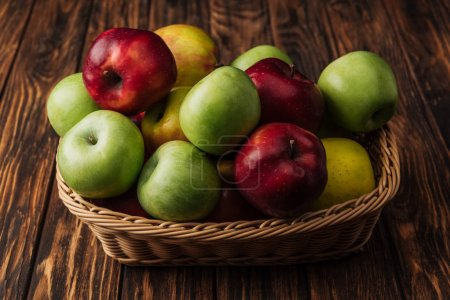 wicker basket with delicious red, green and yellow apples on wooden table