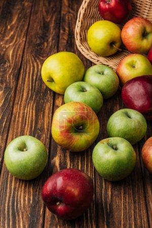 Foto de Encuentran dispersos manzanas multicoloras y cesta de mimbre en mesa de madera - Imagen libre de derechos