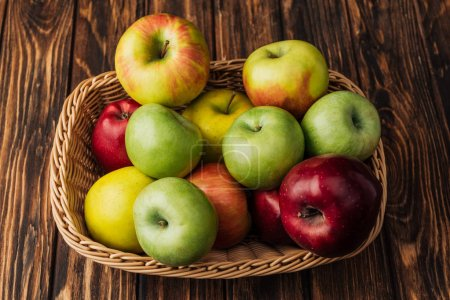 Photo for Wicker basket with ripe multicolored apples on rustic wooden table - Royalty Free Image