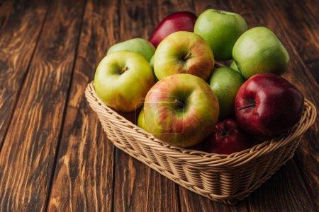 ripe multicolored apples in wicker basket on rustic wooden table
