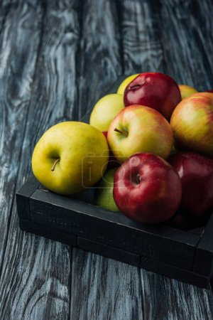 Photo for Wooden box with ripe multicolored apples on grey table - Royalty Free Image