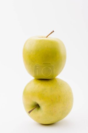 Photo for Stack of two ripe golden delicious apples on white background - Royalty Free Image