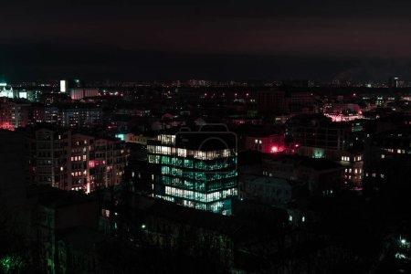 Photo pour Paysage urbain sombre la nuit avec des fenêtres éclairées - image libre de droit