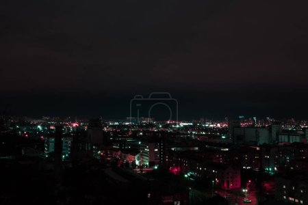 Photo for Dark cityscape at night with multicolored illuminated windows - Royalty Free Image