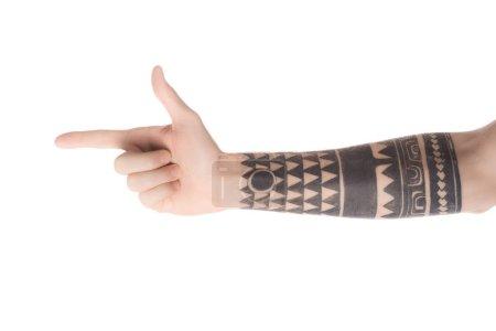 Photo pour Vue recadrée homme tatoué pointant à gauche avec le doigt isolé sur blanc - image libre de droit
