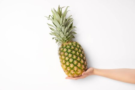cropped view of woman holding sweet pineapple in hand on white background