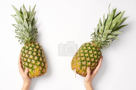 cropped view of woman holding pineapples in hands on white background