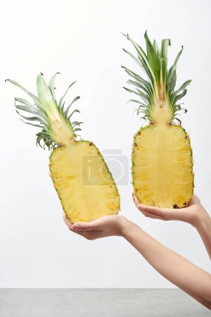 cropped view of woman holding yellow pineapple halves isolated on white