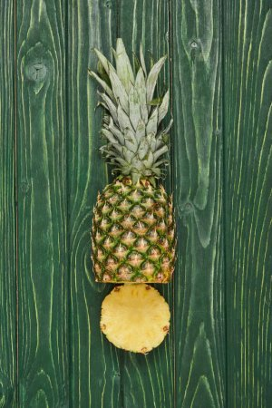 top view of sliced pineapple on green wooden table