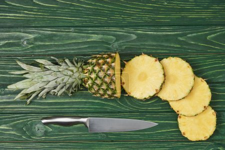 top view of sliced circles of ripe pineapple on green wooden table
