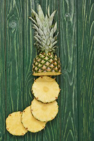 top view of sliced circles of tasty pineapple on green wooden table