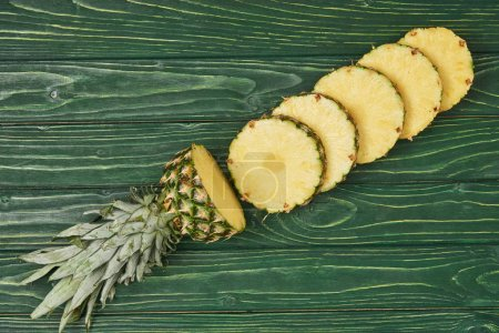 top view of sliced circles of yellow ripe pineapple on green wooden table