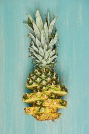 Photo for Top view of sliced yellow pineapple on turquoise wooden table - Royalty Free Image